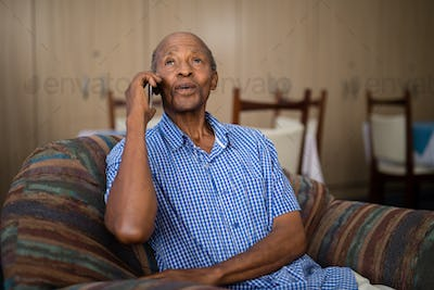 Senior man talking on mobile phone while sitting on sofa