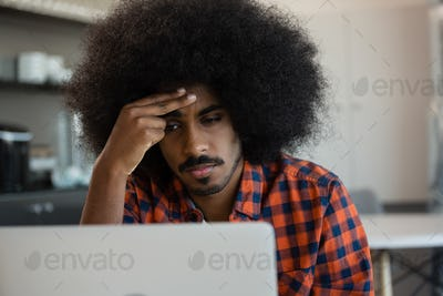 Tired man looking into laptop at office