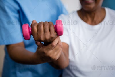 Midsection of nurse guiding senior woman in lifting dumbbell