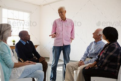 Man talking to friends sitting on chair