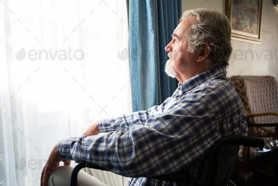 Senior man looking through window while sitting on wheelchair in retirement home