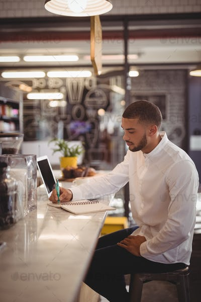 Side view of young male owner writing on notepad at counter