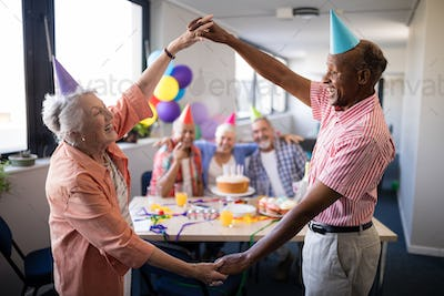 Senior couple making frame against friends at birthday party