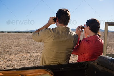 Rear view of couple by off road vehicle looking through binoculars