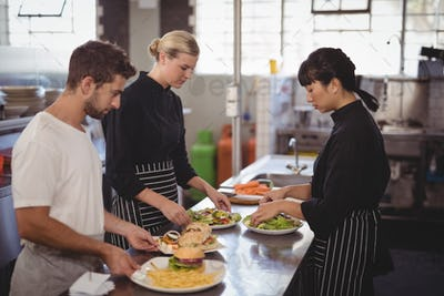 Young wait staff with fresh food in plates on kitchen counter