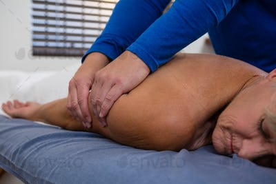 Physiotherapist giving hand massage to a senior woman