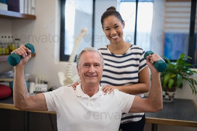 Portrait of smiling female doctor standing with male patient lifting dumbbells