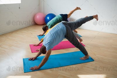 Male instructor with students practicing downward facing dog pose with feet up