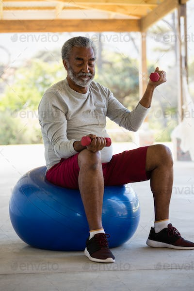 Senior man exercising with dumbbells on exercise ball in the porch