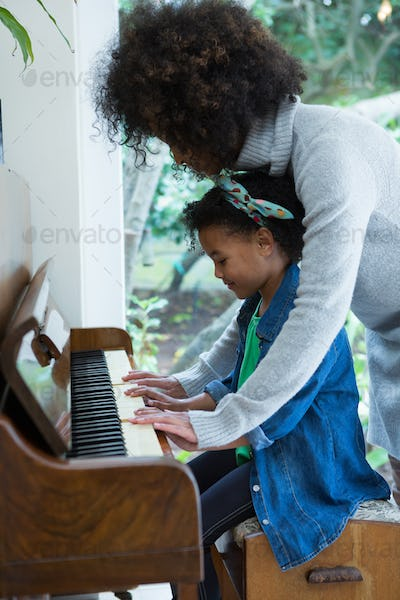 Mother assisting daughter in playing piano