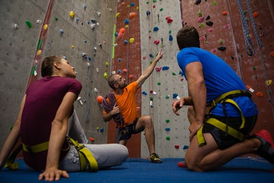 Male trainer guiding athletes in wall climbing at gym