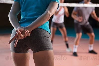 Mid section of player gesturing at volleyball court