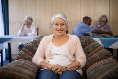 Portrait of happy senior woman sitting on couch