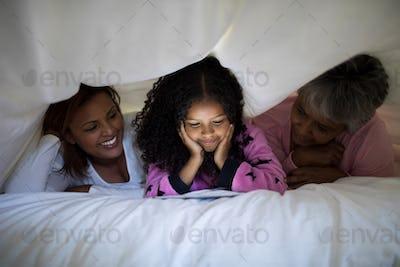 Happy family using digital tablet under blanket in bedroom