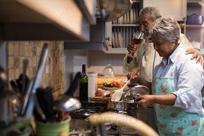 Man having wine while woman preparing food
