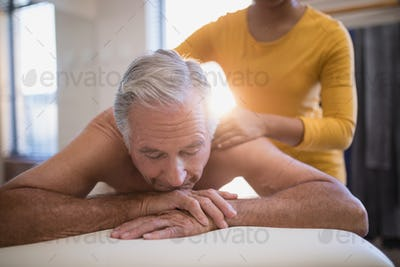 Shirtless male patient lying on bed receiving neck massage from young female therapist