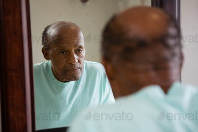 Mirror with reflection of concerned senior man
