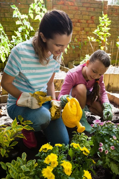 Smiling mother kneeling by girl watering plants
