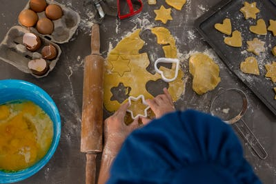 Cropped image of boy preparing cookies