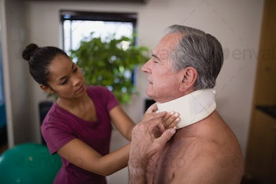 Female therapist examining neck collar on senior male patient