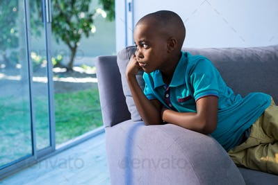 Thoughtful boy looking away while sitting on sofa