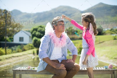 Daughter in angel costume adjusting crown on father head