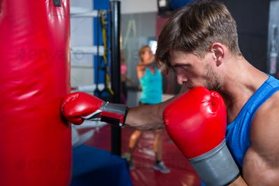 Side view of young male boxer punching red bag