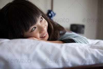 Smiling girl resting on bed