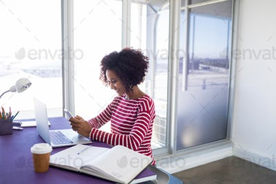 Female executive using mobile phone while working over laptop
