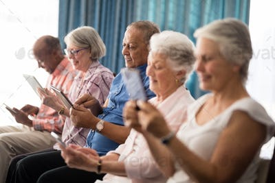 Smiling senior people using digital tablets while sitting on chairs