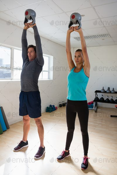 Trainer with athlete lifting kettlebells in gym