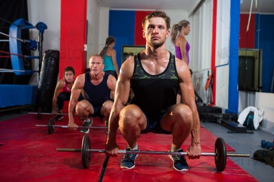 Young athletes crouching with barbells