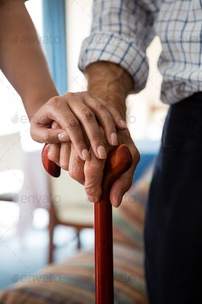 Hands of female doctor and senior man holding walking cane in retirement home