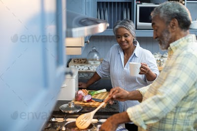 Smiling woman with coffee cup standing by man preparing food