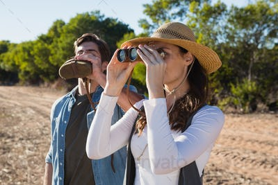 Young woman looking through binoculars while boyfriend drinking water in forest
