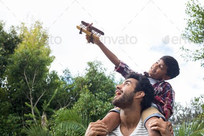 Boy playing with airplane while sitting on fathers shoulder