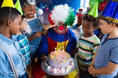 High angle view of children with clown standing by cake
