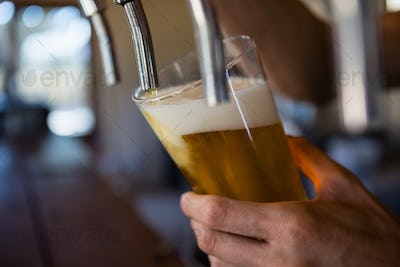Cropped hand of bartender pouring beer from tap in glass