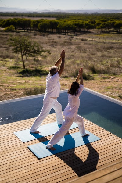 Couple practicing yoga on at poolside