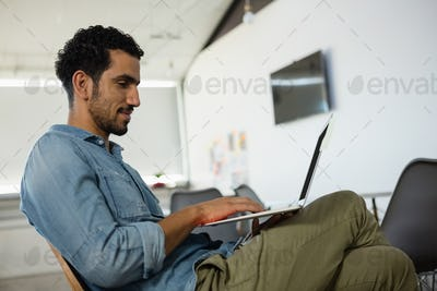 Relaxed man using laptop in office