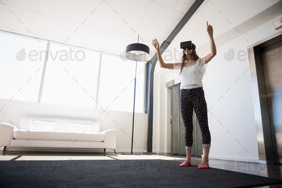 Full length of businesswoman wearing virtual reality simulator
