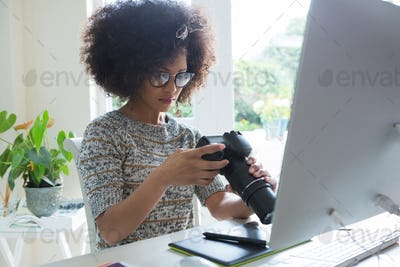 Graphic designer reviewing pictures on digital camera