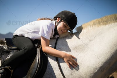 Smiling girl embracing the white horse in the ranch
