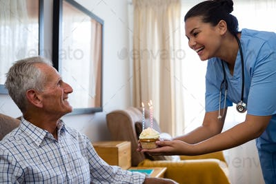 Happy senior man looking at doctor holding cup cake with candle in nursing home