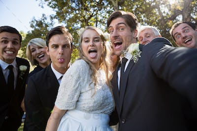 Happy couple posing with guests during wedding