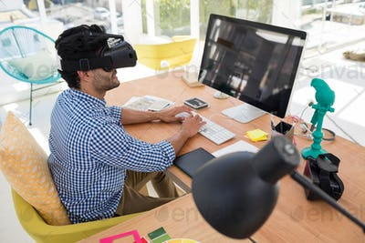 Graphic designer in virtual reality headset working on computer at desk