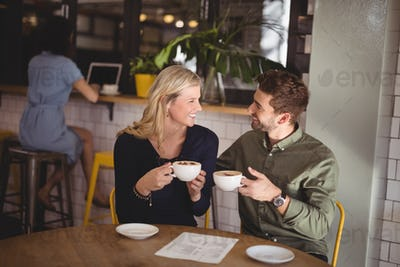 Smiling couple holding fresh coffee cups while sitting at cafeteria