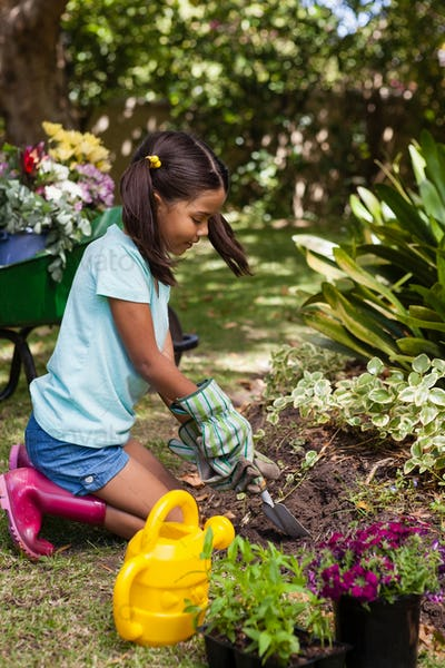 Side view of girl kneeling while digging soil with trowel