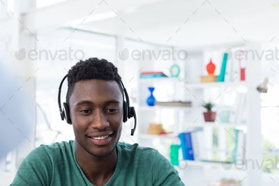 Male executive in headset at his desk in office