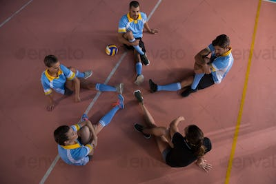 High angle view of volleyball players warming up with coach